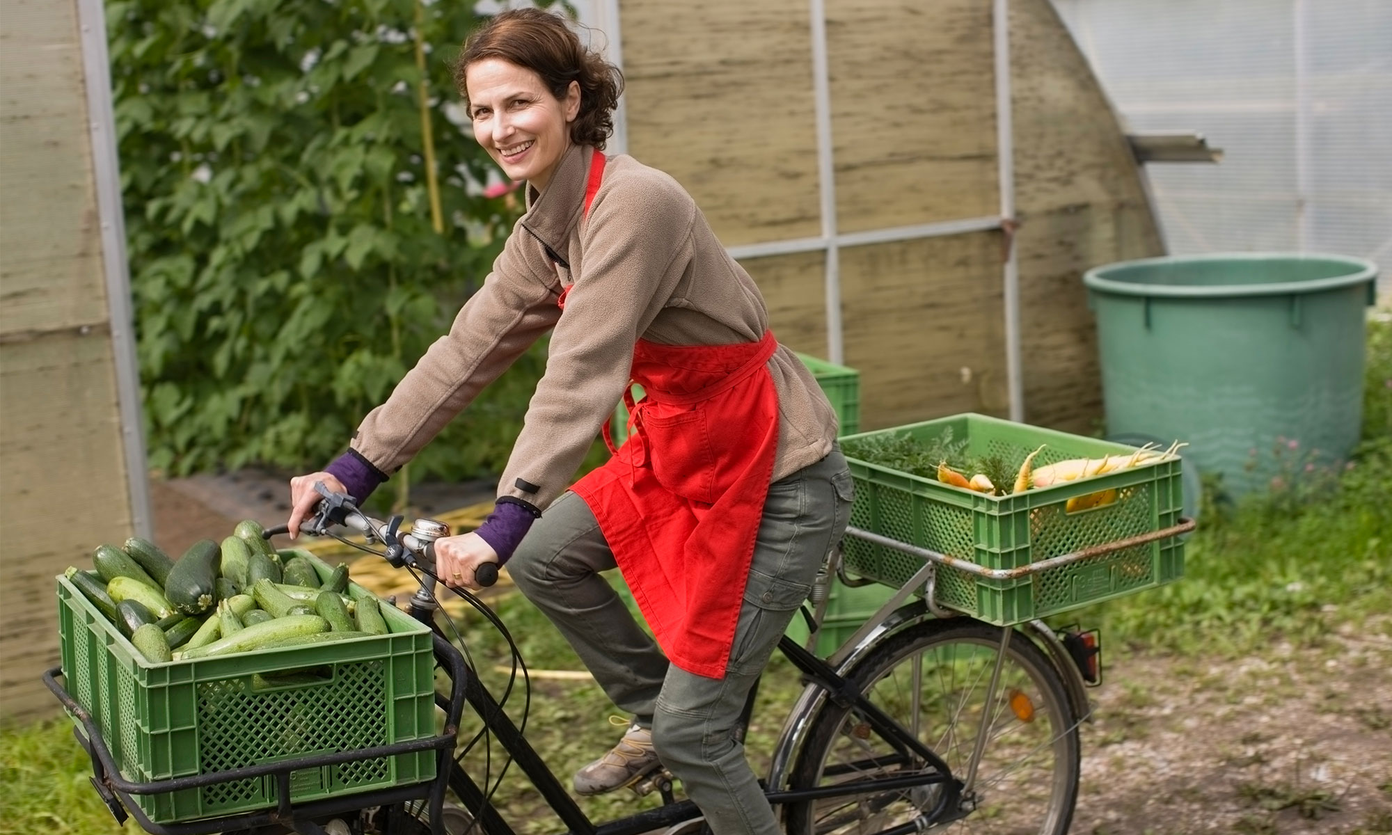 Woman on a bike carrying vegetables.