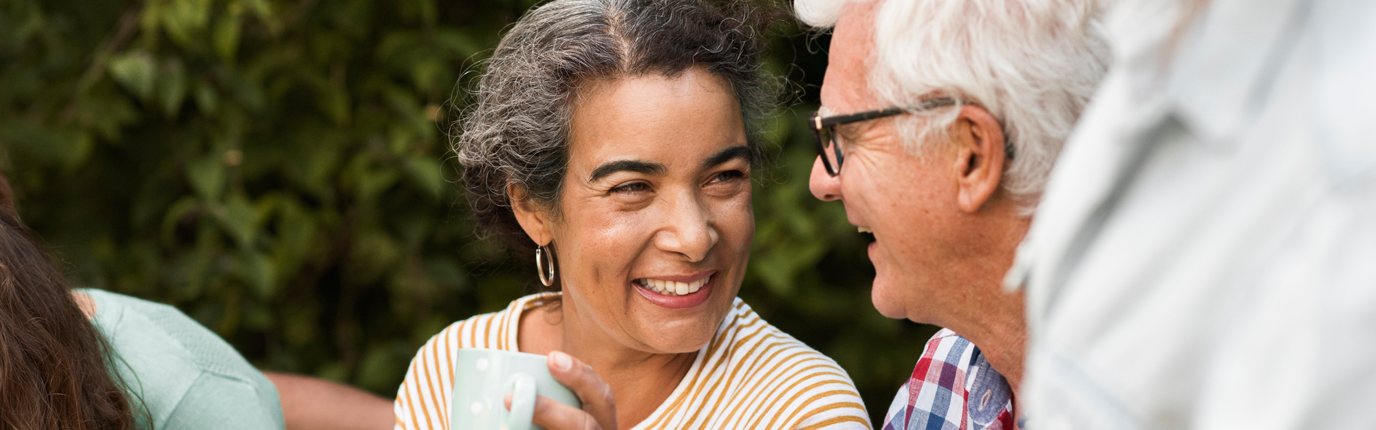 Smiling woman holding coffee cup with older man.